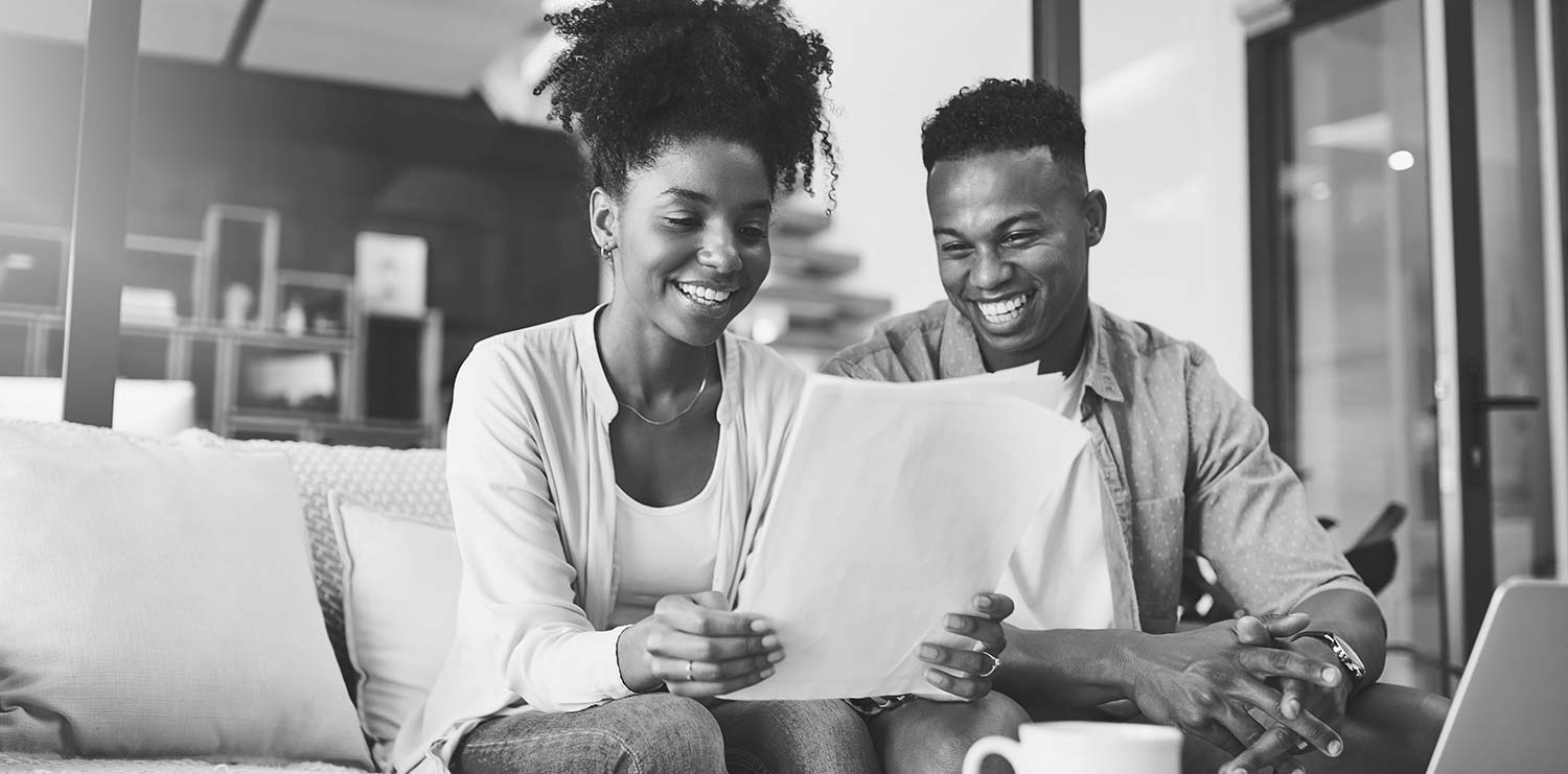 Two people smiling and looking at papers